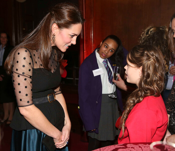 Kate with baby bump talking to child