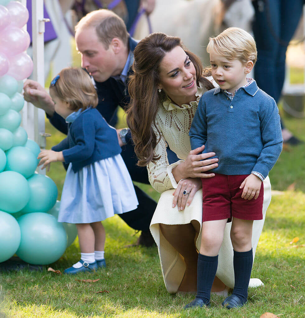 William and Kate playing with kids with balloons that are blue and pink