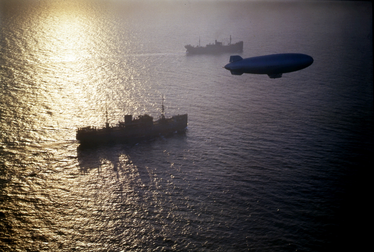 View of two unidentified merchant cargo ships from a convoy as they are escorted by a K-Class patrol blimp, mid 1940s.