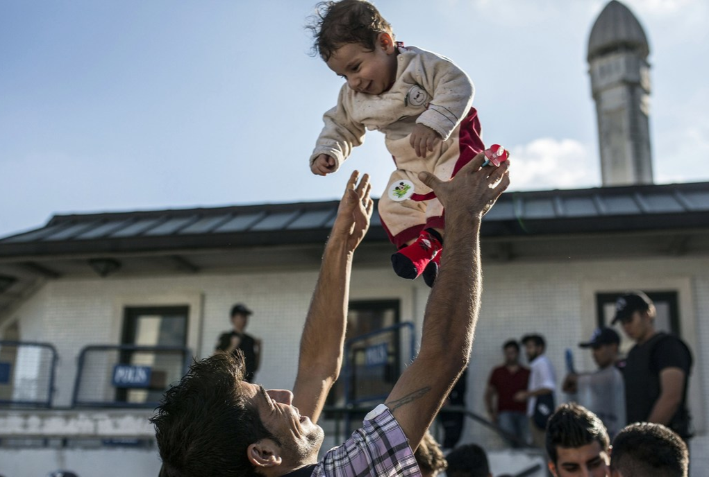 A migrant man throws his baby in the air at Istanbul's Esenler Bus Terminal while waiting for buses