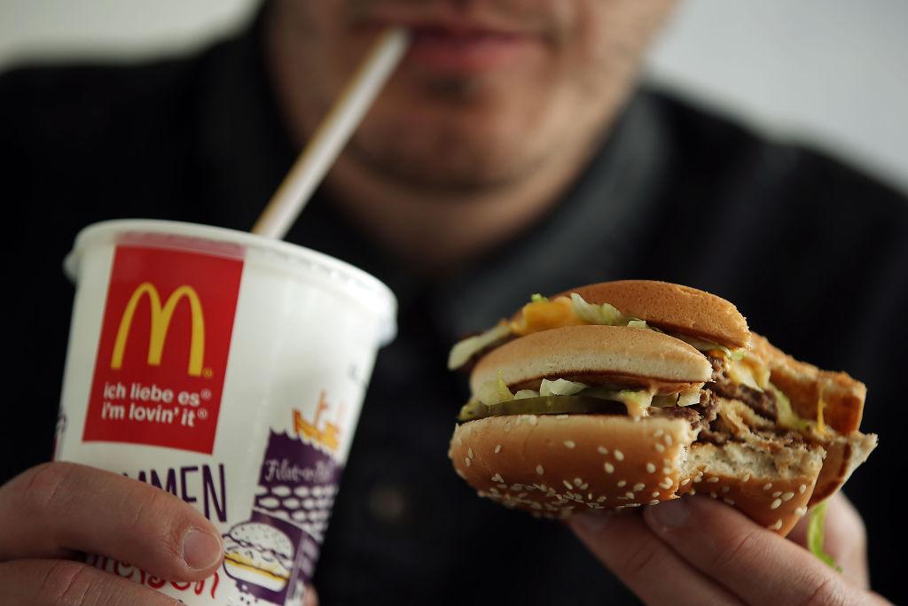 A man drinks a coke and eats a Big Mac burger
