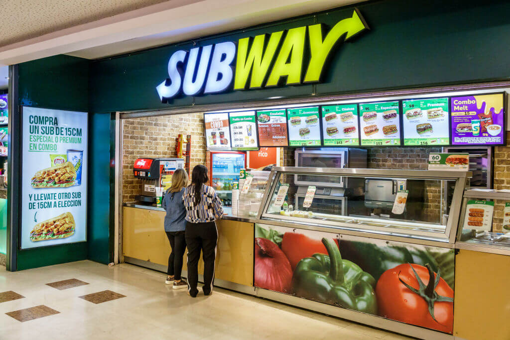 two women standing to order at subway restaurant