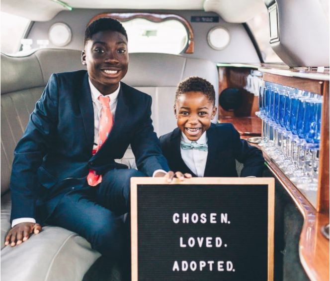 "Dayshawn and Michael shank hold a sign that says ""chosen, loved, adopted"" in a limo after the court hearing"