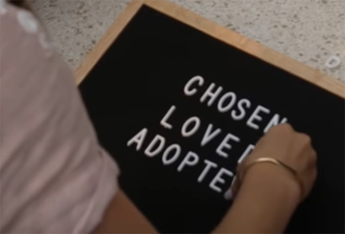 "Sara Cozad makes a sign that says ""Chosen, Loved, Adopted"""