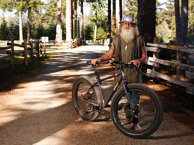 Mick poses with a bike on a gravel trail