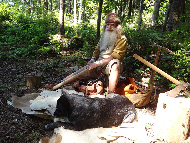 Mick sits in a resting spot in the woods with his dog and belongings