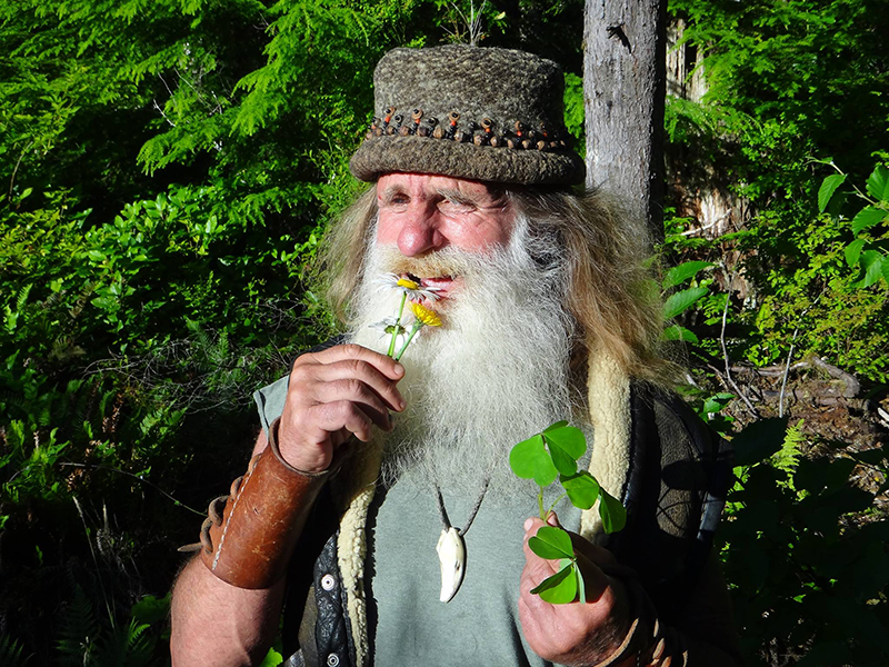 Mick bites at a small yellow flower while holding clovers in his other hand
