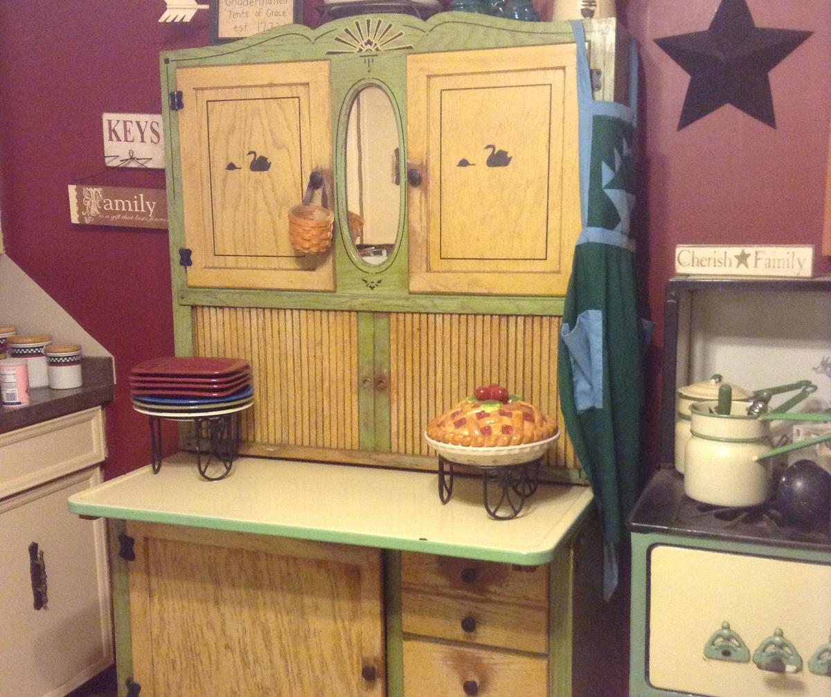 A cream and green oak Hoosier desk sits in a kitchen.