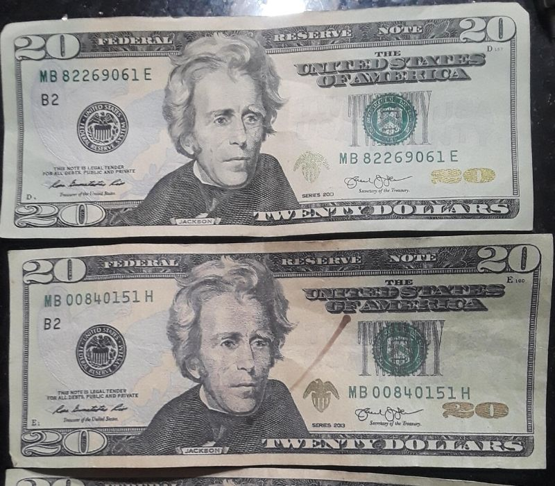 two $20 bills one real one fake