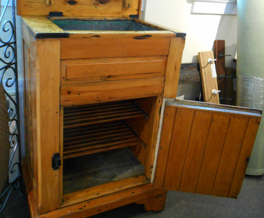 An antique wooden ice box is open.