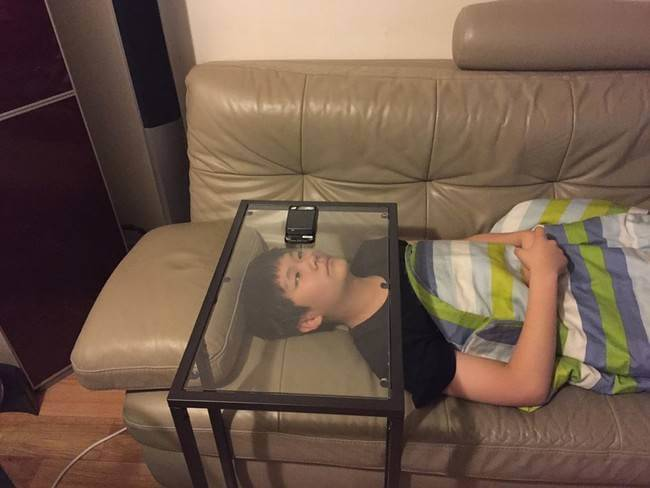 kid laying on couch watching iphone through glass table