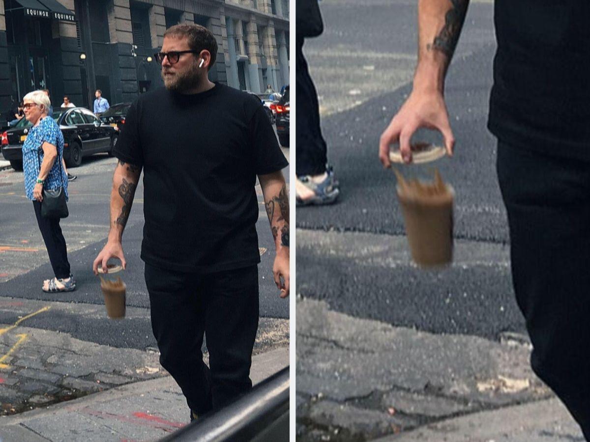 jonah hill walking down street while coffee drops