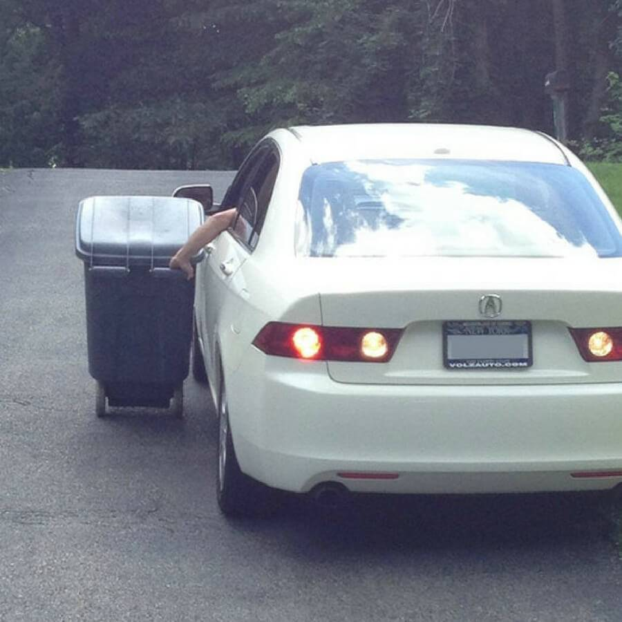 person driving their garbage pail down the driveway