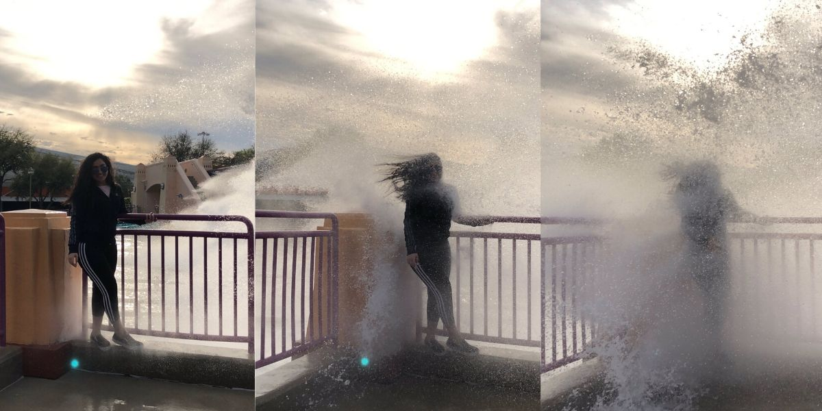 girl soaked by a wave while taking picture