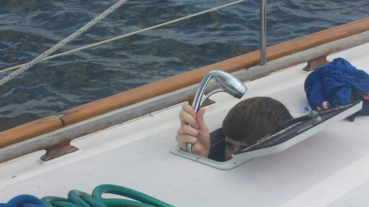 Person with head and shower head peaking out hole in boat