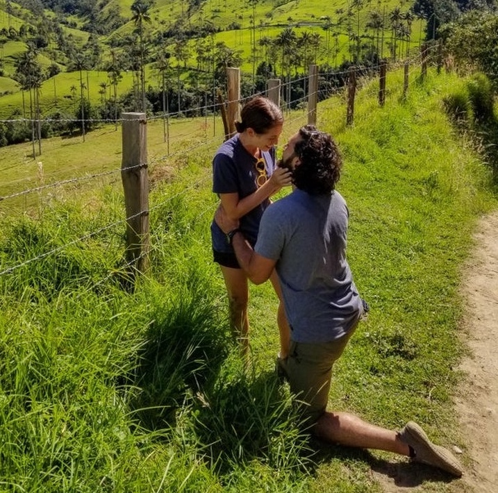 Man on one knee for marriage proposal is same height as standing girlfriend