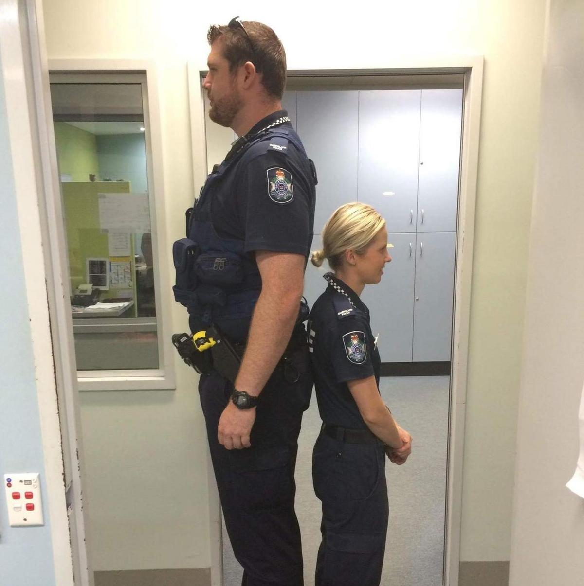 tall male and short female police officers back to back
