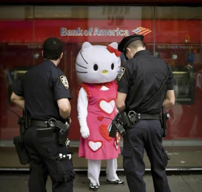Someone dressed as Hello Kitty is interrogated by police outside of a building.
