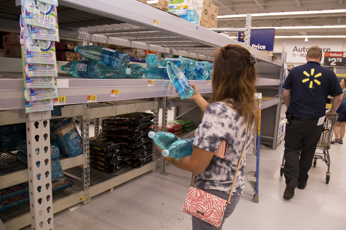 Diana Francisco grabs an armful of the few remaining bottles of water at a Walmart.