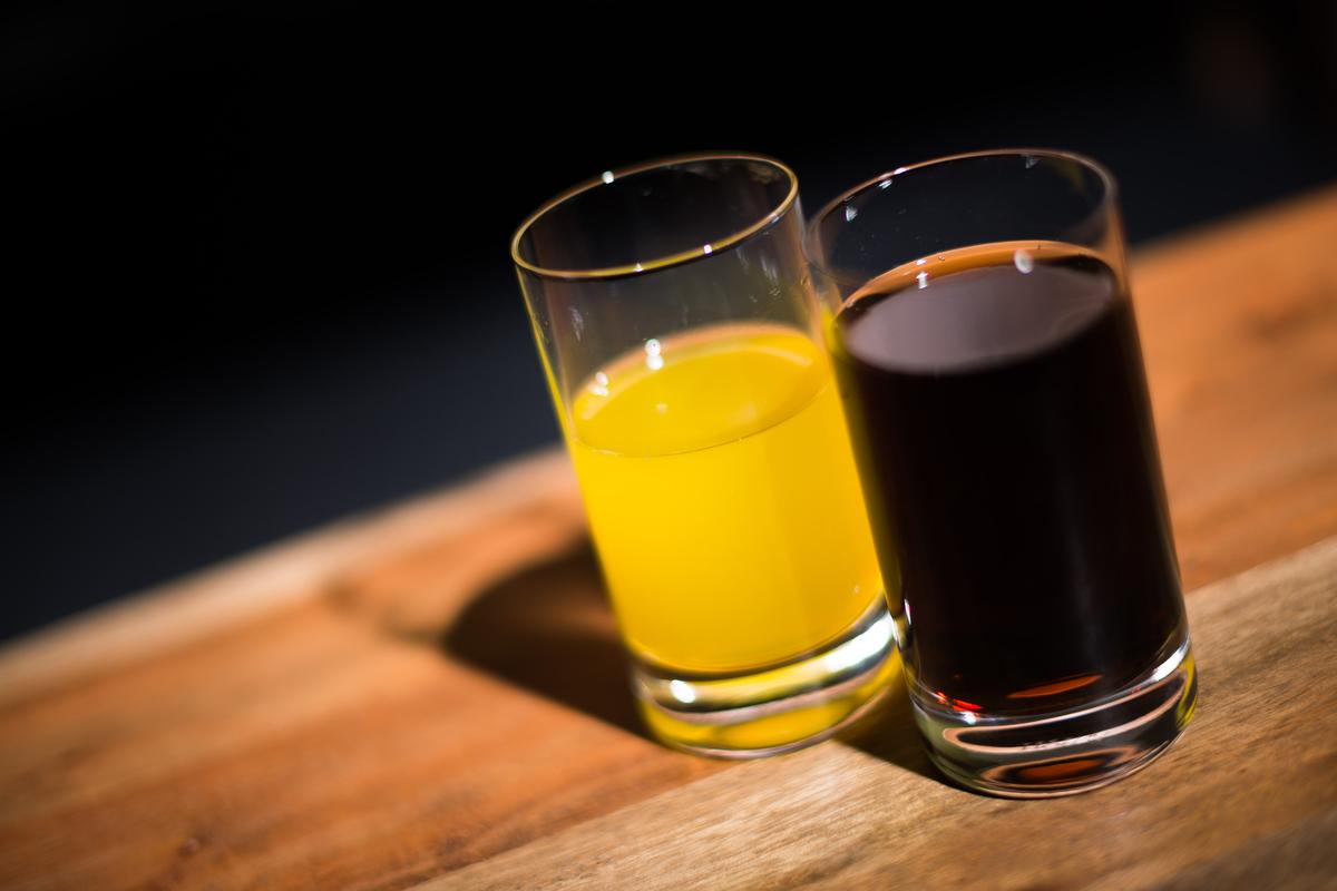 A glass of coca cola sits next to a glass of orange lemonade.