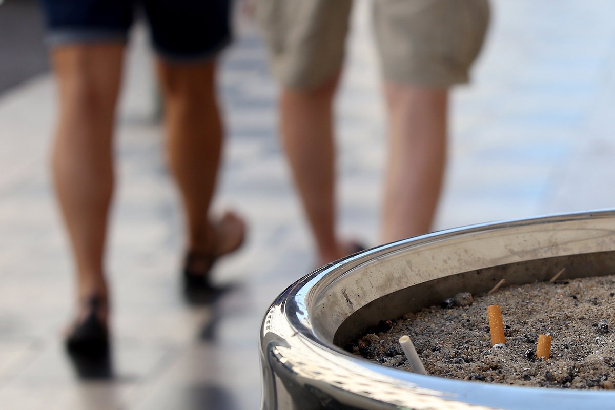 Two people walk away from an ashtray.