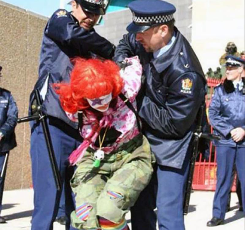 A woman dressed up as a clown leans down while two officers try to handcuff her.