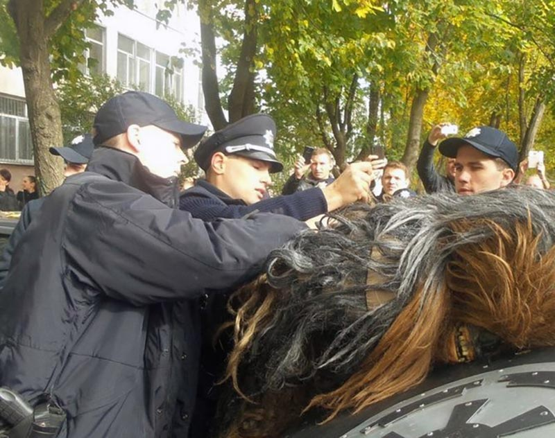 Someone in a Chewbacca costume is leaned over and handcuffed by police.