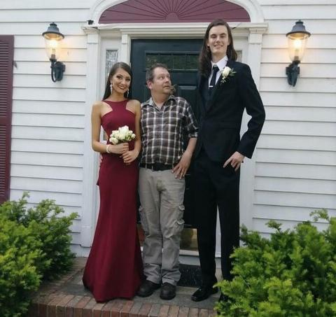 dad looking up at daughter's tall prom date