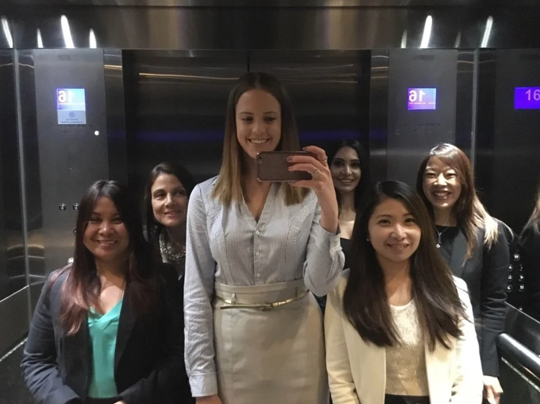 girl in mirrored elevator takes selfie with coworkers who are all significantly shorter than her