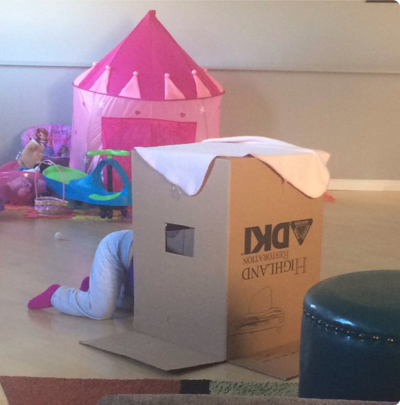 a kid playing in the box her new castle came in