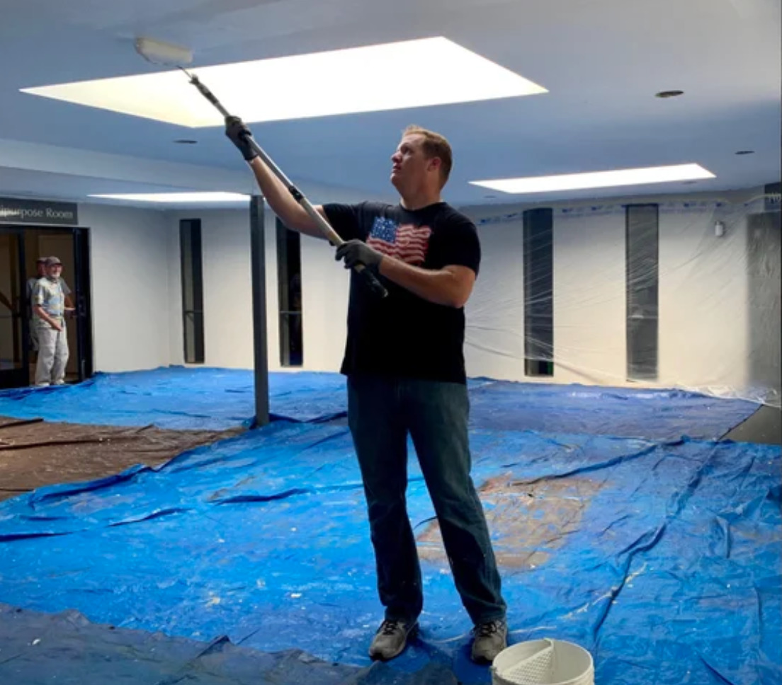 tall man painting ceiling
