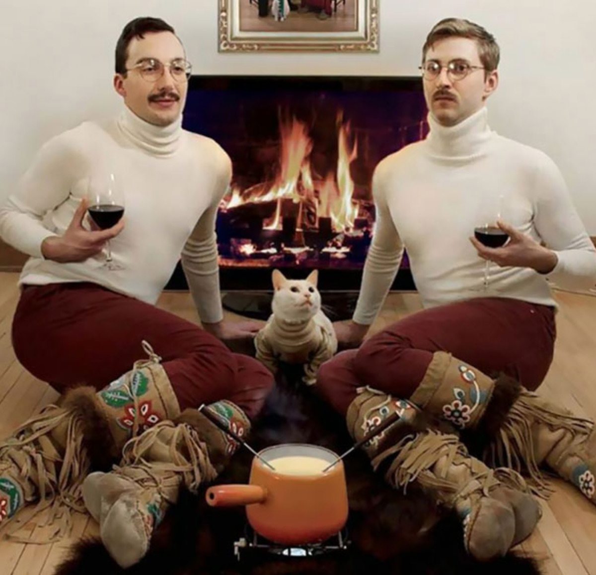 two guys in matching outfits (their cat has the same sweater too) with apot of fondue