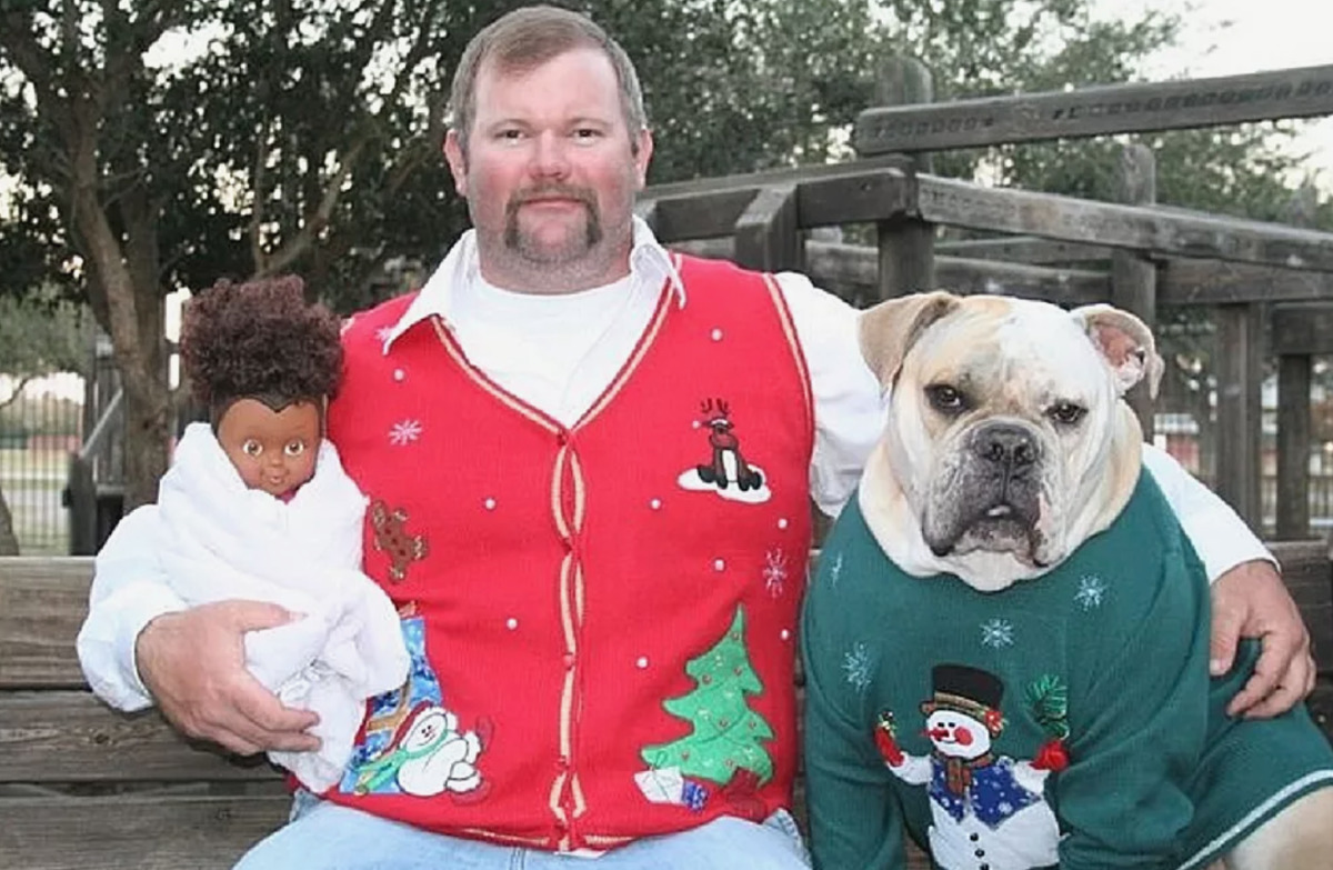 man in christmas vest with dog and baby doll