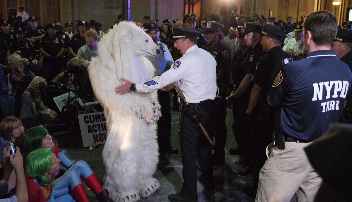 A crowd of people surround and officer as he arrests someone in a polar bear costume.