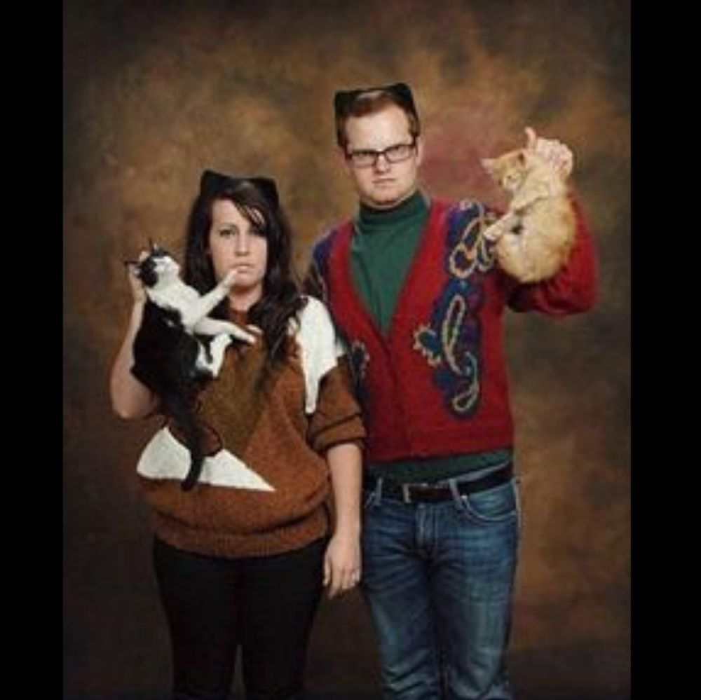 couple hold cats by the neck and look angry