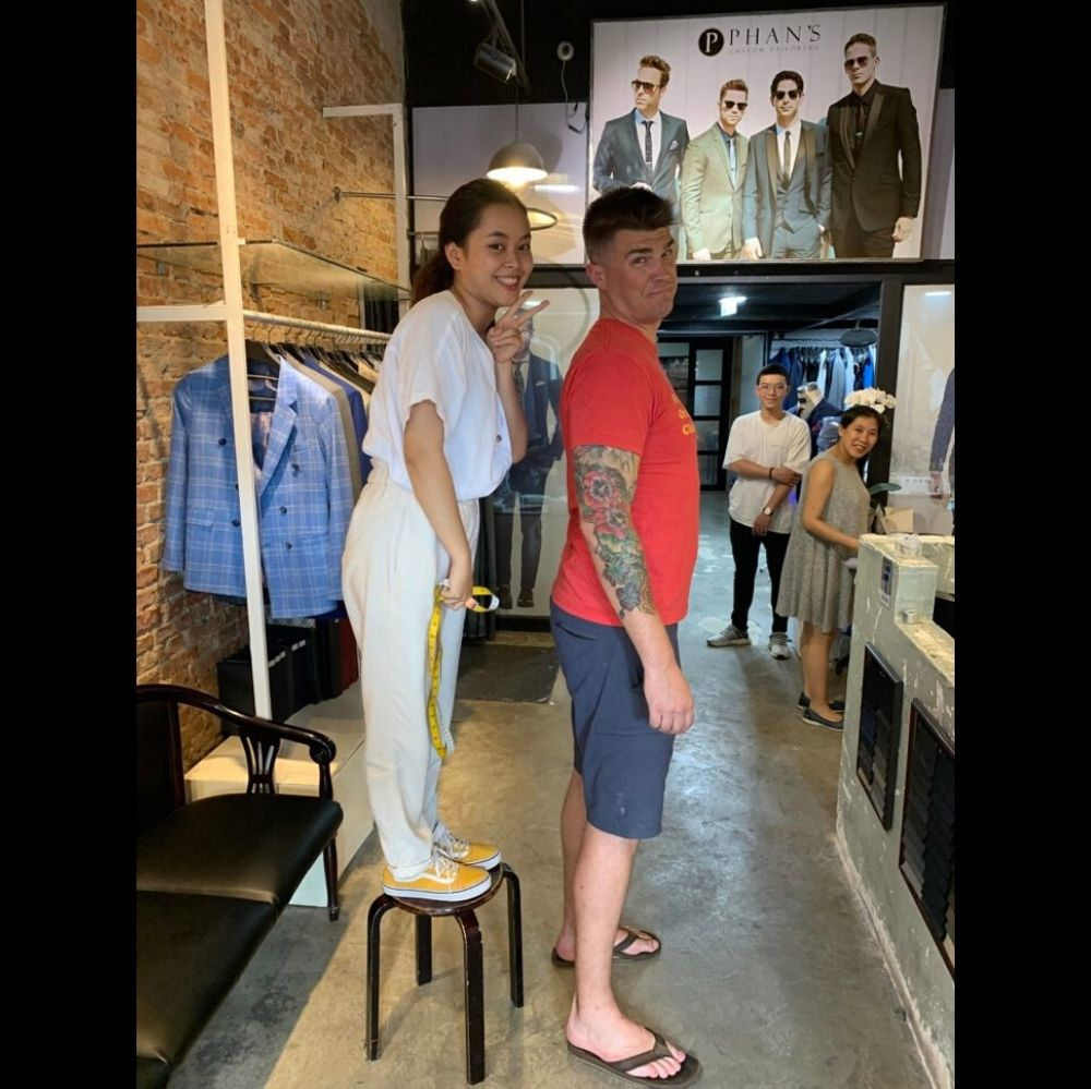 Tailor has to stand on stool to take man's measurments