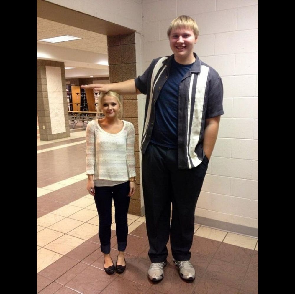 Tall man with arm out over short girl's head