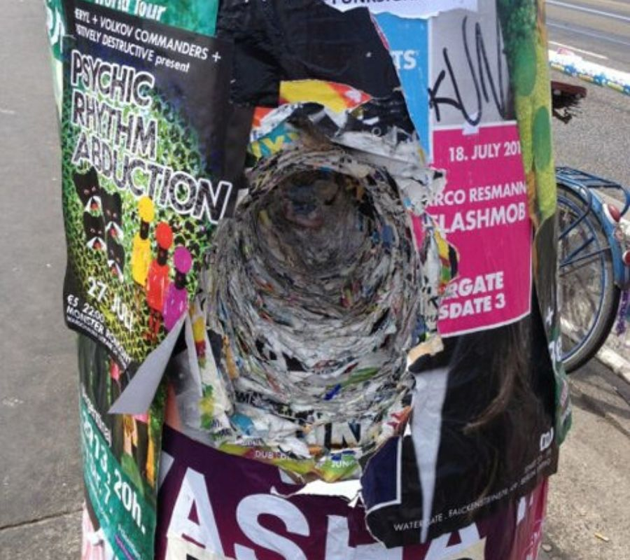 layers of posters on a pole