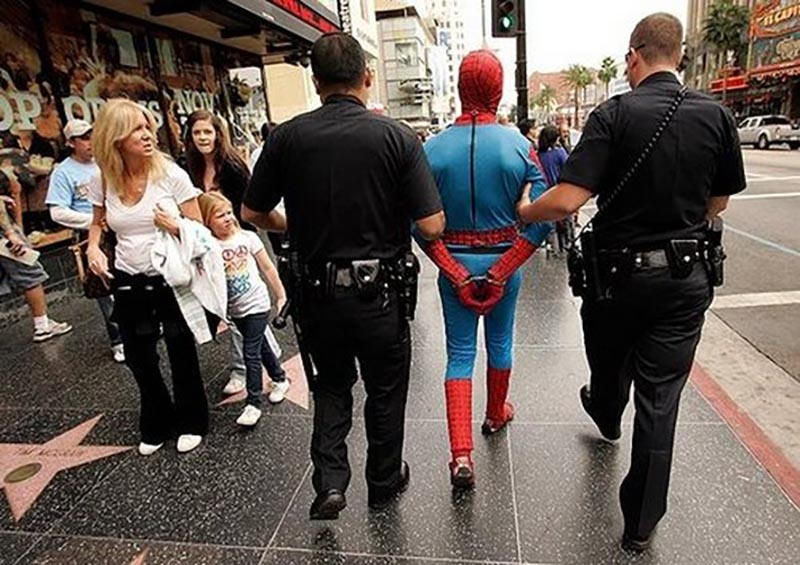 Spiderman walks in handcuffs between two escorting officers.
