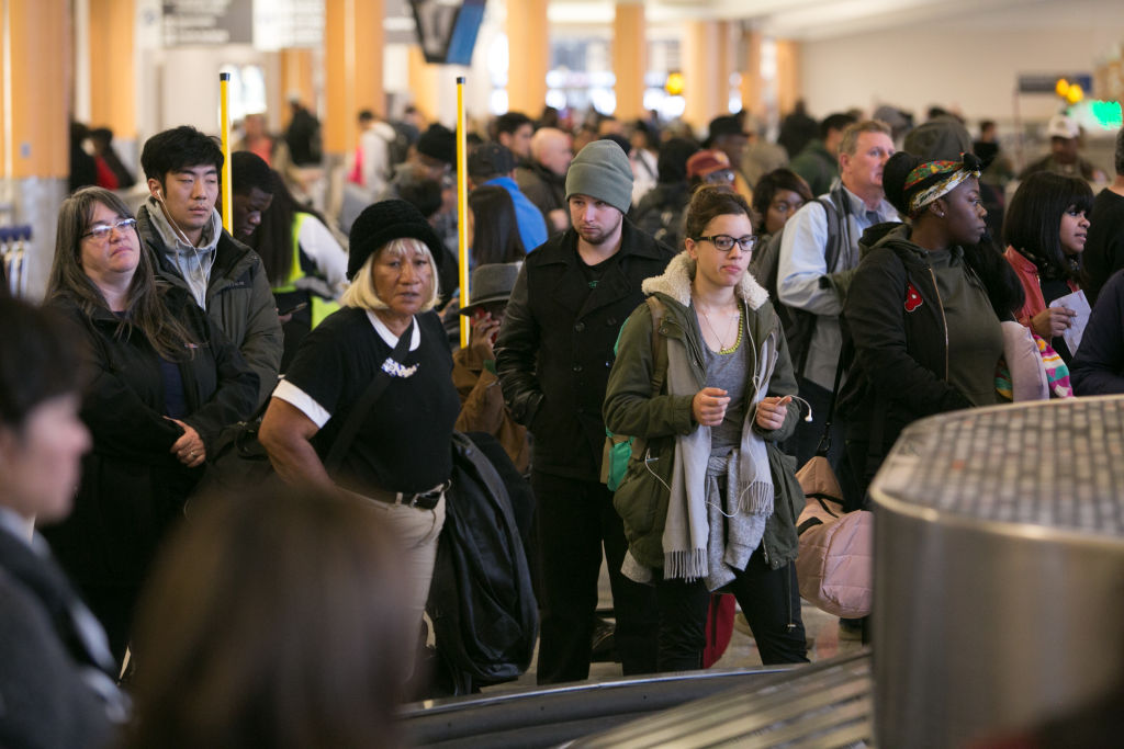 Passengers wait for baggage to arrive on the carousel