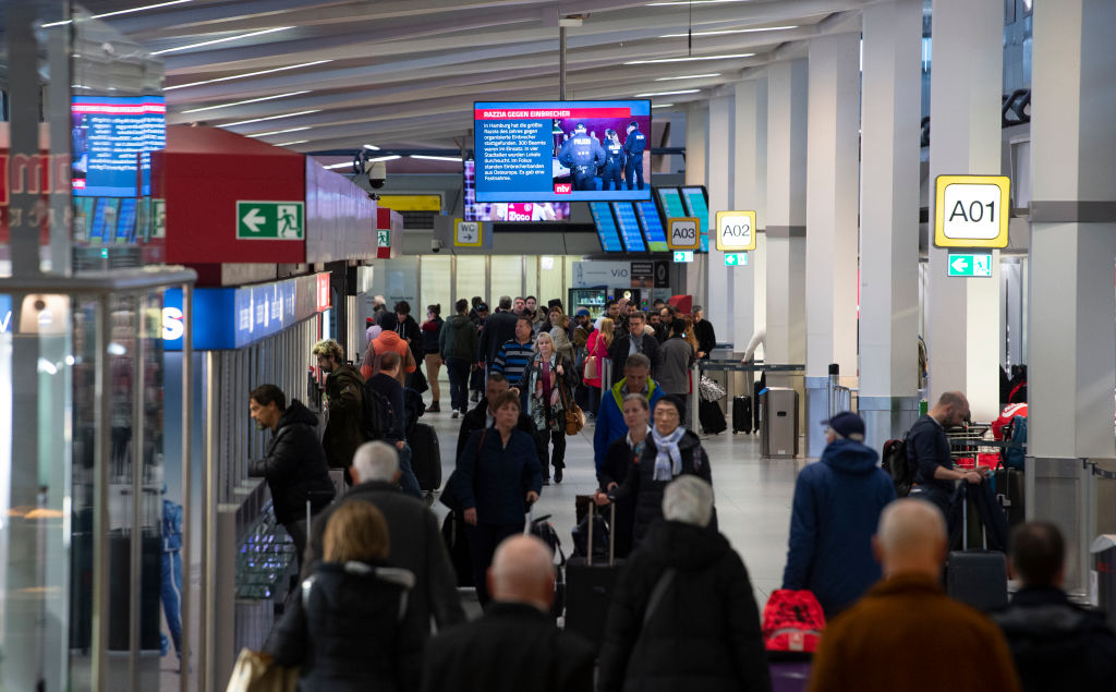 Passengers go to the terminal at Tegel Airport.