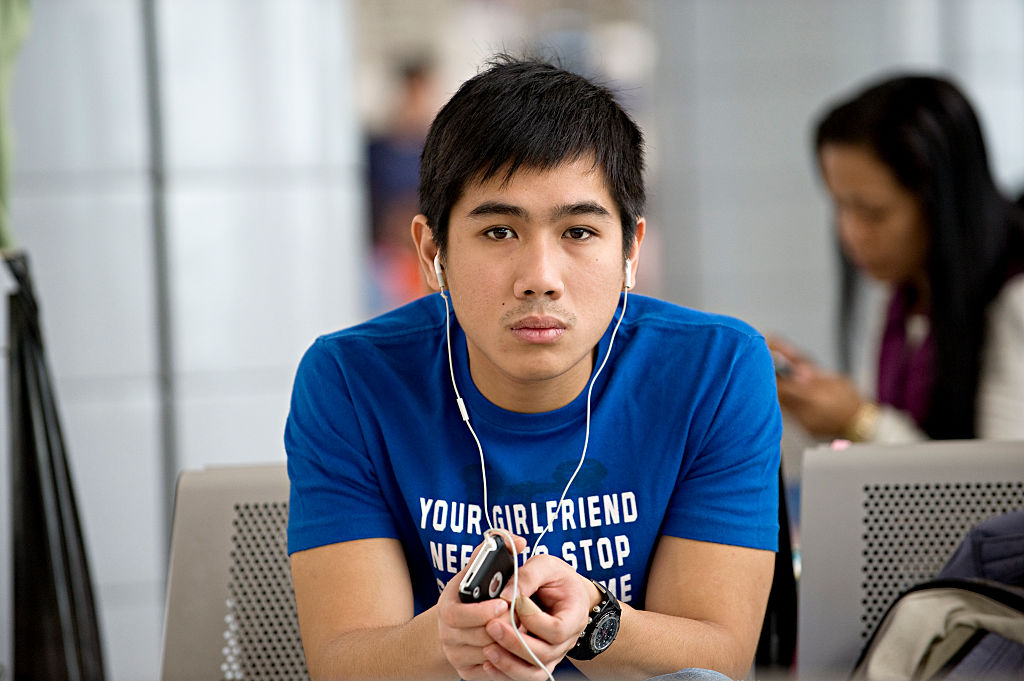 A young traveller sits in the Manila airport waiting for his departure. (
