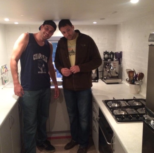Two men standing in kitchen with heads touching ceiling