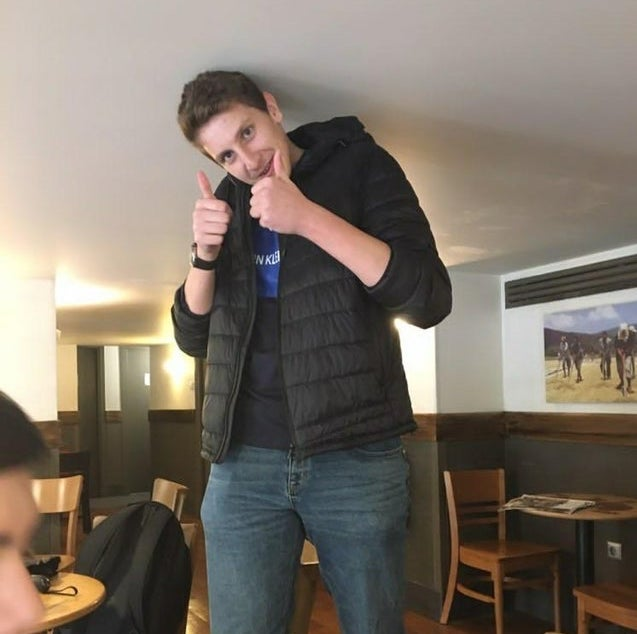 Man in cafe has head touching ceiling when he stands