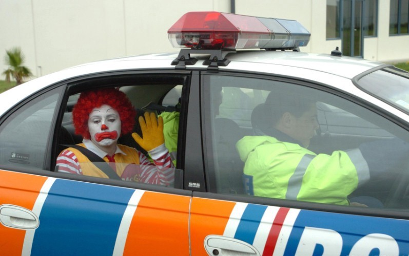 A frowning McDonald's clown waves from the backseat of a cop car.