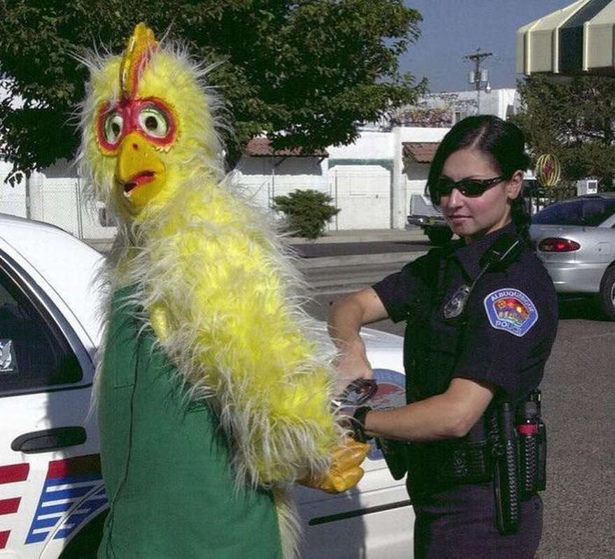 A person dressed in a chicken costume and a police officer look into the camera while she arrests the chicken.