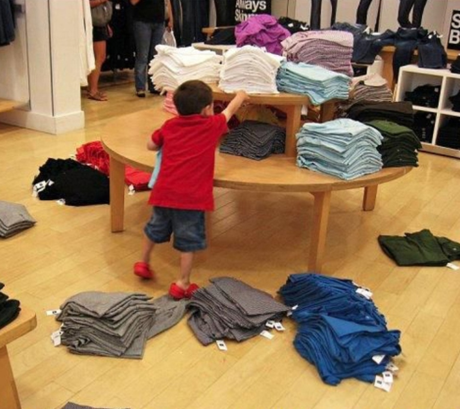 a kid pulling shirts off a display in the store