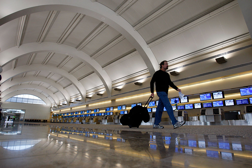 A traveler walks past new flat panel screens