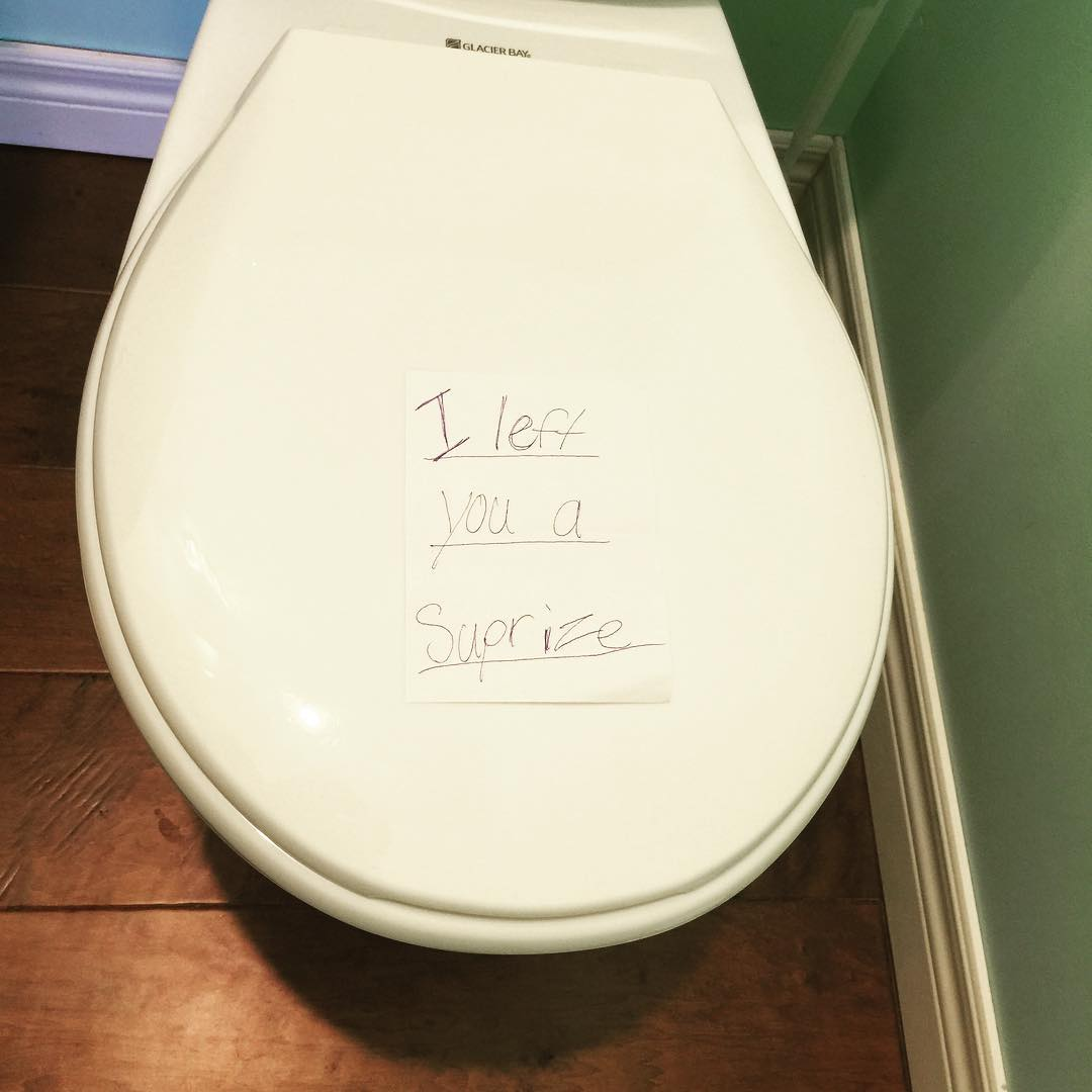 a toilet lid closed with a note on it that says 'I left you a surprise'