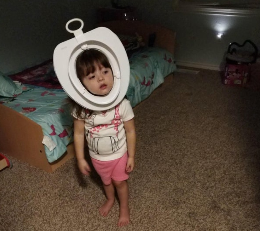 a little girl wearing a toilet training seat